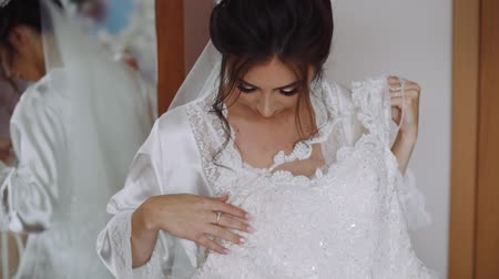 cerimônia : Beautiful Bride Smiling and Looking at her White Wedding Dress. Morning Wedding Preparations of Young Lovely Bride. Happy Marriage and Wedding Day Concept