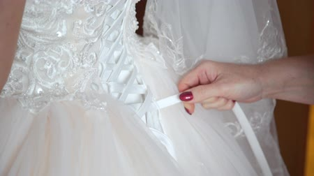 espartilho : Hands of Mother of Bride Lacing Up White Wedding Dress. Morning Wedding Preparations. Happy Marriage and Wedding Day Concept