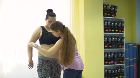 жир : Personal Trainer Measuring Overweight Woman in a Gym after Workout. Slow Motion. Healthcare, Sport, Fitness, Weight Losing, Nutrition and Active Lifestyle Concept