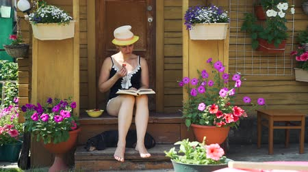 sundurma : Young Woman Reading Novel and Eating Strawberry while Sitting on the Porch of a Beautiful Country House with Lots of Pots with Flowers. The Dachshund Dog Lying near Her on the Step of Porch. Stok Video