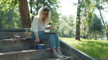 şaheser : Female Painter Working with Watercolor in the City Park in Sunny Summer Day in Slow Motion. Blonde Woman Artist Painting a Picture on the Street. Art, Creativity and People concept Stok Video