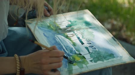 шедевр : Close Up of Female Artist Drawing Picture with Watercolor in a City Park. Painting with Brush and Watercolor in a Summer Day. Creativity Inspiration Expression Concept
