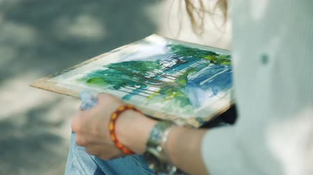 obra prima : Close Up of Female Artist Painting a Picture of Embankment while Sitting in a City Park. Street Artist Drawing Outdoors with Watercolor in Summer Day. Creativity Inspiration Expression Concept Stock Footage