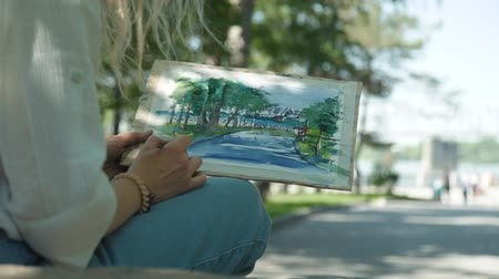obra prima : Female Artist Painting River Embankment with Watercolor in Summer Day. Woman Drawing in the Street. Slow Motion. Art, Creativity and People concept