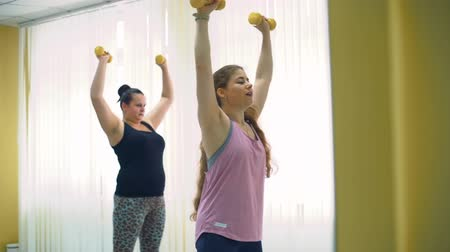 tamanho : Plump Woman Doing Exercises with Personal Trainer in a Gym in Slow Motion. Oversized Female Doing Exercises with Dumbbells. Healthcare, Sport, Fitness, Weight Losing, Active Lifestyle Concept Vídeos