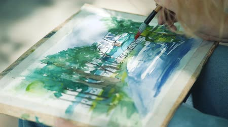 obra prima : Highly Gifted Street Artist Drawing with Watercolors in a City Embankment in Sunny Summer Day. Creativity Inspiration Expression Concept Stock Footage