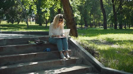 obra prima : Professional Painter Working in a City Park in Sunny Summer Day while Sitting on Steps. Female Street Artist Doing a Sketch for Future Picture Outdoors. Creativity Inspiration Expression Concept Stock Footage