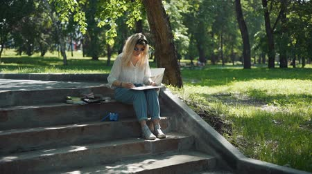 шедевр : Female Street Artist Doing a Sketch for Future Picture Outdoors in Slow Motion. Professional Painter Working in a City Park in Sunny Summer Day while Sitting on Steps.