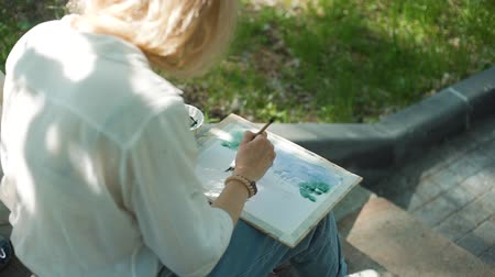obra prima : Female Street Artist Drawing with Watercolor in a City Park while Sitting on Steps. Woman Painting a Picture on the Street. Slow Motion. Art, Creativity and People concept Stock Footage