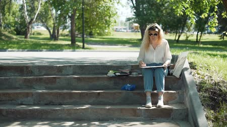 шедевр : Female Street Artist Painting a Picture Outdoors in Sunny Summer Day. Professional Painter at Work in a City Park. Slow Motion. Art, Creativity and People concept