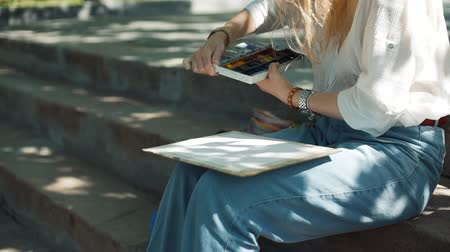 obra prima : Female Street Artist Preparing to Draw a Picture in a Park with Watercolor in Sunny Summer Day. Creativity Inspiration Expression Concept Stock Footage