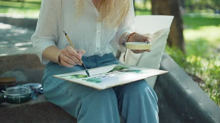 obra prima : Female Artist Working On Painting Outdoors. Watercolor Painting Outdoors in Summer Day. Slow Motion. Art, Creativity and People concept
