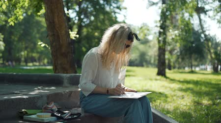 obra prima : Woman Artist Preparing a Sketch for Future Picture. Professional Painter at Work in a City Park in Sunny Summer Day. Art, Creativity and People concept