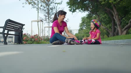 inline skating : Happy Little Girl and her Mom Spending Free Time Together Outdoors. Mother and Daughter Sitting on the Bicycle Lane after Rollerblading in a City Park. Slow Motion. Summer Family Activities Concept Stock Footage