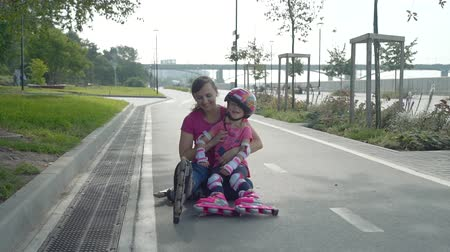 inline skating : Little Girl and her Mother Having Fun after Rollerblading in Slow Motion. They are Sitting on the Bicycle Lane in a City Park in Sunny Day. Summer Family Activities Concept Stock Footage