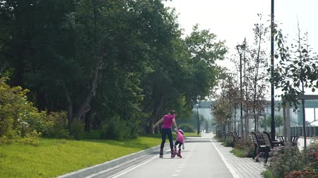 inline skating : Little Girl Learning to Roller Skate with Mother in a City Park in Sunny Day. Slow Motion. Back Side View. Active Family Lifestyle Concept Stock Footage
