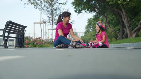 inline skating : Mother and Daughter Sitting on the Bicycle Lane after Rollerblading in a City Park. Happy Little Girl and her Mom Spending Free Time Together Outdoors. Active Family Lifestyle Concept Stock Footage
