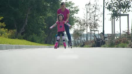 inline : Young Mother Teaching her Cute Little Daughter to Ride Roller Skates. Girl and Woman Rollerblading in a City Park in Sunny Summer Day. Slow Motion. Active Family Lifestyle Concept