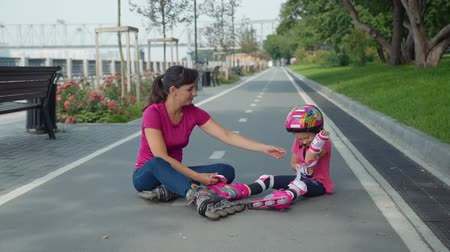 inline skating : Mother and her Daughter Sitting on the Bicycle Lane after Rollerblading in a City Park. Little Girl in the Colorful Sport Helment Taking Off her Protective Gear with Help of her Mother.