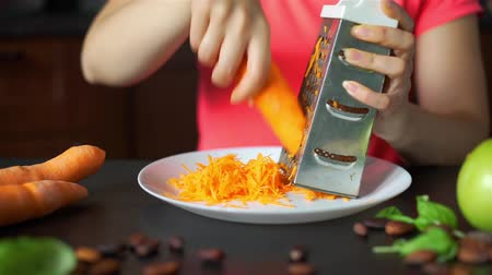 reibe : Hands of Woman Rubbing Carrots on a Grater in the Kitchen. Close Up. Healthy Eating, Cooking, Vegetarian Food and Dieting Concept Videos