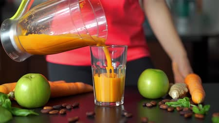 juice jar : Close Up of Woman Pouring Freshly-made Vegetable Smoothie from Blender into a Glass in the Kitchen. Slow Motion. Healthy Lifestyle, Weight Loss Food and Nutrition Concept