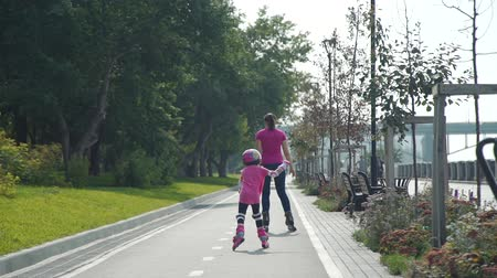 inline skating : Little Girl Roller skating with her Mother in the City Street in Sunny Day. Back view. Active Family Lifestyle Concept