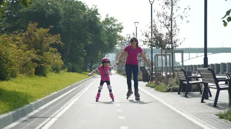 inline : Young Mother and her Little Daughter Roller Skating Together in a City Park in Summer Day. Slow Motion. Active Family Lifestyle Concept