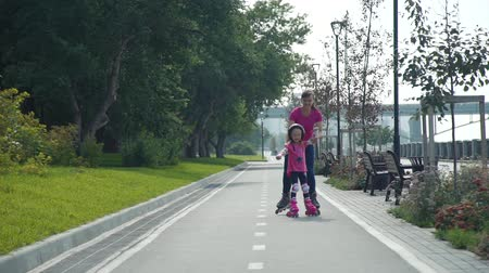 inline skating : Little Girl Practicing Roller Skates with her Mother in a City Park. Summer Family Activities Concept Stock Footage