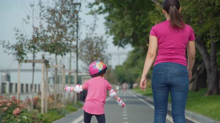inline : Little Girl with her Mother Roller skating on Sunny Promenade in Slow Motion. Back Side View. Active Family Lifestyle Concept Stock Footage