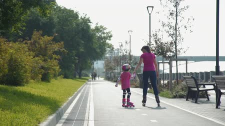 inline skating : Little Girl Learning to Roller Skate. Young Mother Teaching Daughter to Ride on Rollers in Slow Motion. Back view. Active Family Lifestyle Concept Stock Footage