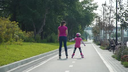 inline : Little Girl with Mother Riding on Roller skating Outdoors in Slow Motion. Young Woman Teaching Little Girl to Rollerblading in Sunny Day. Active Family Lifestyle Concept Stock Footage