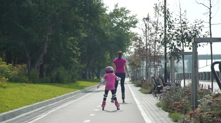 inline : Little Girl Roller skating with her Mother in the City Street in Sunny Day in Slow Motion. Back view. Summer Family Activities Concept