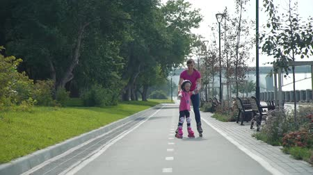inline skating : Little Girl Practicing Roller Skates with her Mother in a City Park in Slow Motion. Active Family Lifestyle Concept