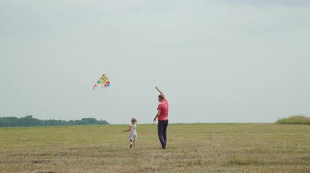 uçurtma : Little Girl and her Father Launching a Colorful Kite in the Autumn Field. Freedom and Family Holiday Concept Stok Video