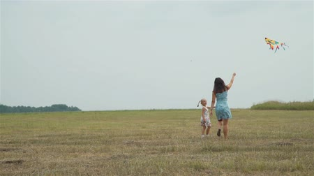 打ち上げ : Young Mother and her Little Daughter Playing a Kite in the Autumn Field. Freedom and Family Holiday Concept