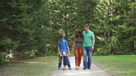 lucfenyő : First Steps of Cute Little Girl with Family Outdoors. Older Brother Teaching Baby to Walk in the Park. Slow Motion. Family, Leisure and People Concept Stock mozgókép