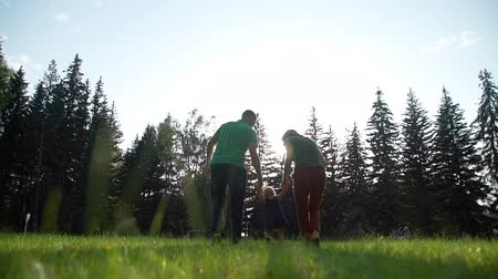 podporující : Parents Teaching Little Daughter to Walk Outdoors. Baby Girl Making her First Steps on a Green Grass, Mother and Father Holding her Hands Supporting by Learning to Walk.