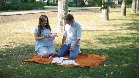 место : Young Man and Woman Looking at Clothes for Their Future Baby in Autumn City Park. Pregnant Couple Preparing to Become Parents. Pregnancy, Maternity, Preparation and Expectation Concept