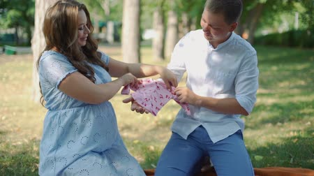фон : Happy Pregnant Woman and her Husband Holding Clothes for Their Future Baby in City Park. Camera Tilting Up. Pregnancy, Maternity, Preparation and Expectation Concept