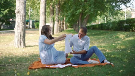 место : Young Man and his Pregnant Wife Looking at Cute White Baby Dress while Sitting on a Plaid in Autumn City Park. Pregnancy, Maternity, Preparation and Expectation Concept