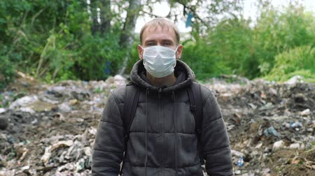 compactor : Portrait of Young Man in a Mask Standing Near the Garbage Pile. Concept of Environmental Pollution and Waste Recycling