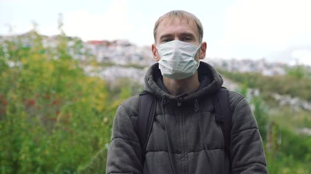 compactor : Portrait of a Young Man Standing in Front of Camera in a Mask near a Landfill. Concept of Environmental Pollution and Waste Recycling