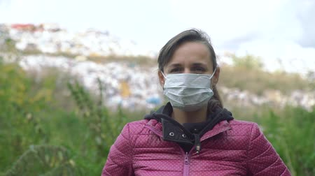 junkyard : Portrait of Young Woman in a Mask Standing near a Landfill. Close Up Shot. Concept of Environmental Pollution and Waste Recycling Stock Footage