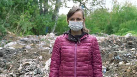 compactor : Young Woman in a Mask Standing Near the Garbage Pile. Landfill Problem. Concept of Environmental Pollution and Waste Recycling Stock Footage