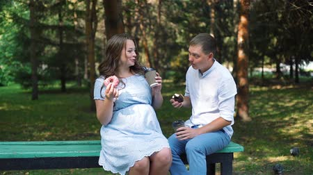 doughnut : Young Man and his Pregnant Wife Having Picnic in the City Park. They Eating Donuts and Drinking Tea while Sitting on the Bench. Slow Motion. The Concept of Family Happiness