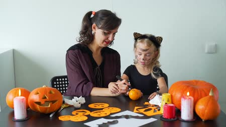 mandarinka : Young Mother and her Little Daughter Making Crafts for Halloween. They are Drawing Scary Face on a Tangerine. Holidays and Halloween Decorations Concept Dostupné videozáznamy