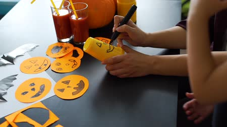 grão : Close Up of Family Making Crafts for Halloween Party. Hands of Young Woman Drawing Scary Face on an Orange Plastic Cup. Holidays and Halloween Decorations Concept