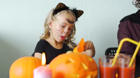 grão : Cute Little Girl Making Crafts from Colored Paper for Halloween with her Mother. Holidays and Halloween Decorations Concept Stock Footage