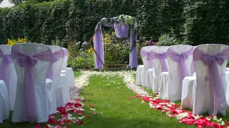 allegiance : Beautiful Wedding Arch Standing near Chairs and Wall of Green Plants. Decorations for Wedding Ceremony Stock Footage