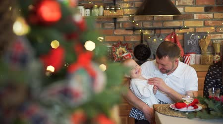 father christmas : Cute Little Girl and her Father Having Fun while Having Dinner at Home. The Family is Enjoying Holidays. Christmas Family Dinner Table Concept Stock Footage